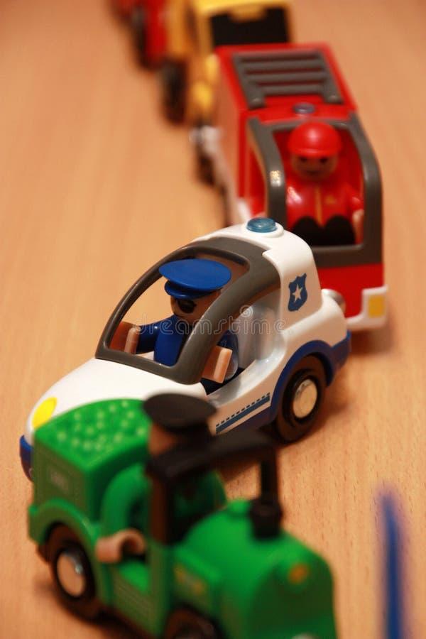 Politiewagen en brandbestrijders in een opstopping van stuk speelgoed auto's stock foto
