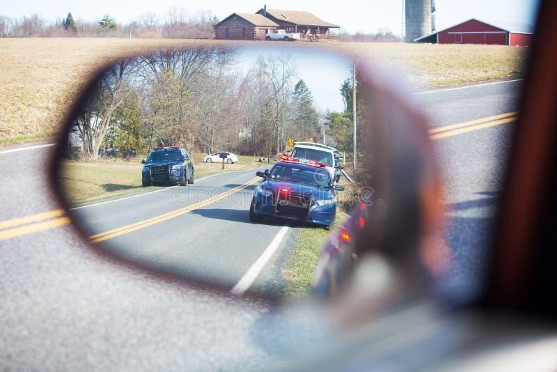 Politiewagen op weg met flitslichten en sirene stock foto's