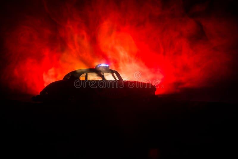 Politiewagens bij nacht Politiewagen die een auto achtervolgen bij nacht met mistachtergrond 911 noodsituatiereactie stock foto