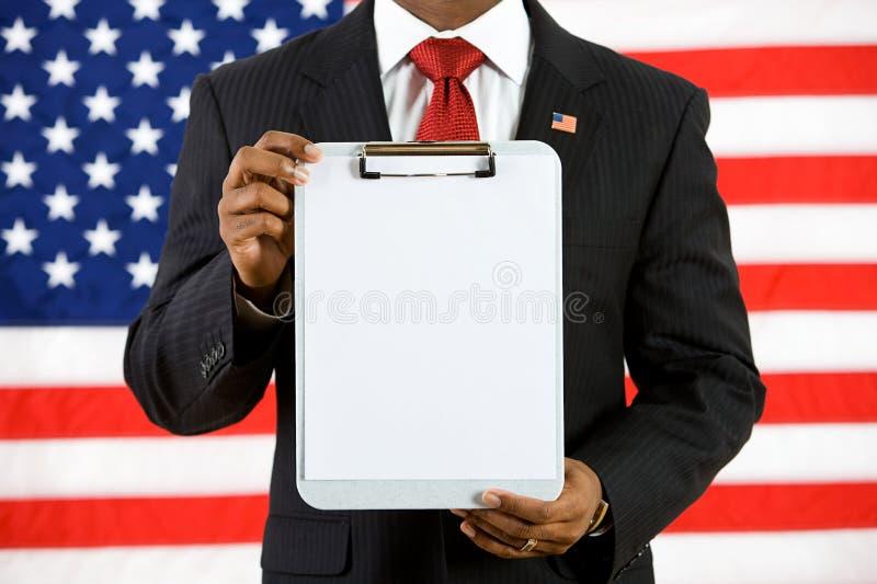 Politiker: Hållande övre en skrivplatta med tomt papper royaltyfria bilder