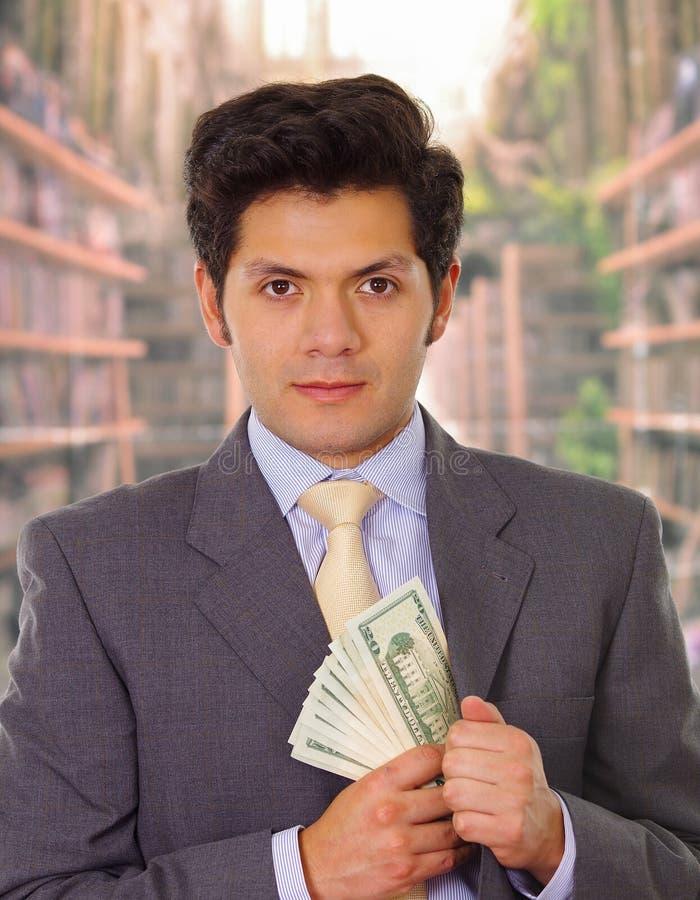 Politiker i mörk dräkt och med bandet som sätter pengar i hans dräkt arkivfoto