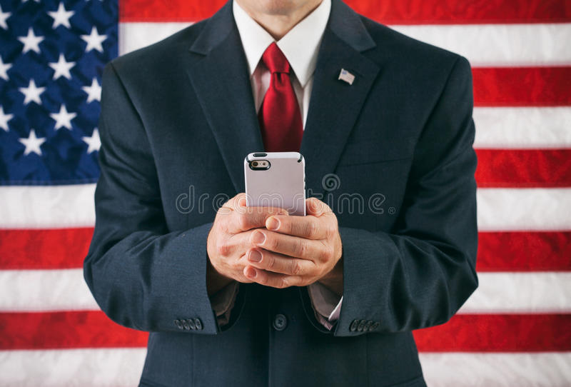 Politiker: Man som smsar på den moderna smarta telefonen royaltyfria foton