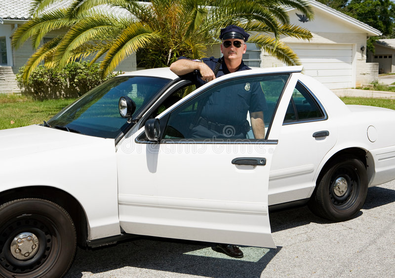Polizei - Offizier u. Polizeiwagen lizenzfreie stockfotografie
