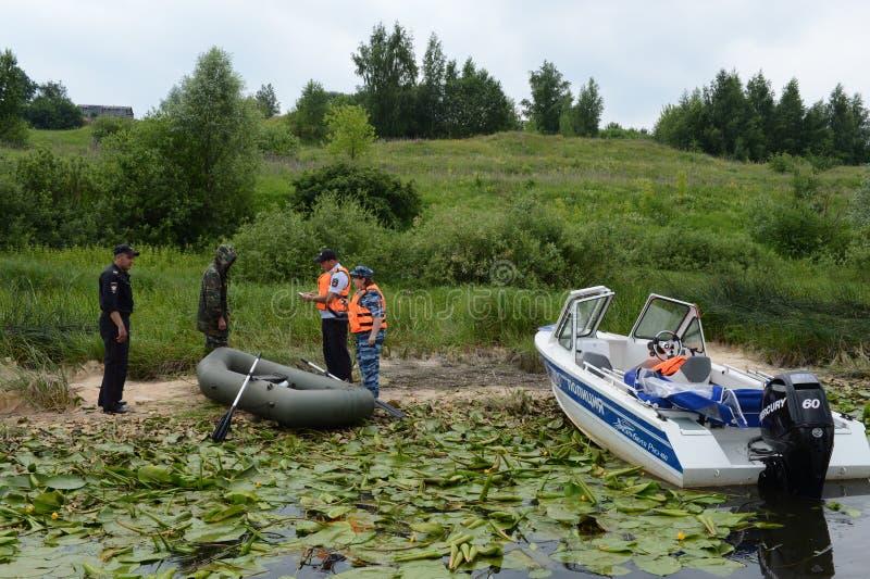 Polizeibeamten stellen ein Protokoll für das Pochieren auf dem Fluss auf lizenzfreie stockfotos