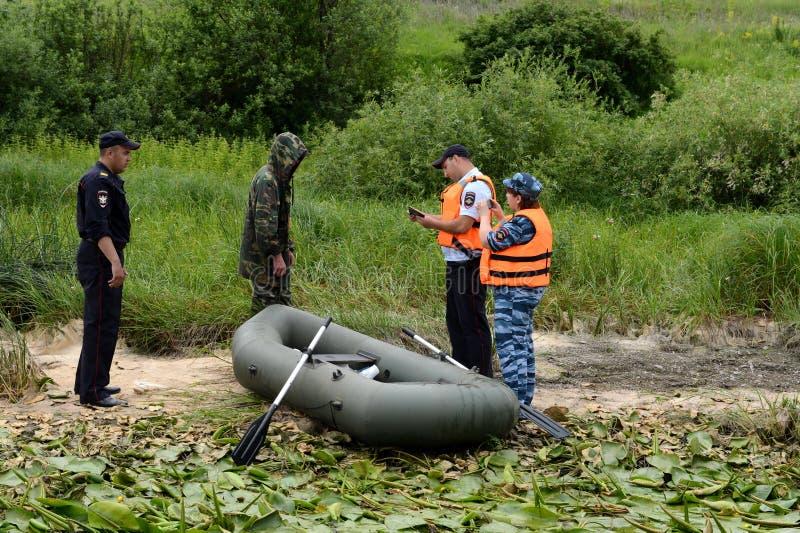 Polizeibeamten stellen ein Protokoll für den Mann für das Pochieren auf dem Oka-Fluss auf stockbilder