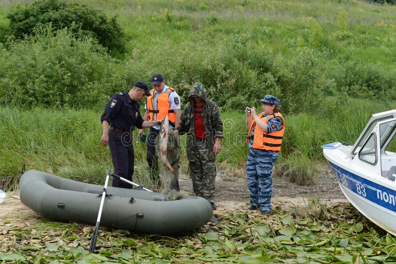 Polizeibeamten stellen ein Protokoll für den Mann für das Pochieren auf dem Oka-Fluss auf lizenzfreie stockfotografie