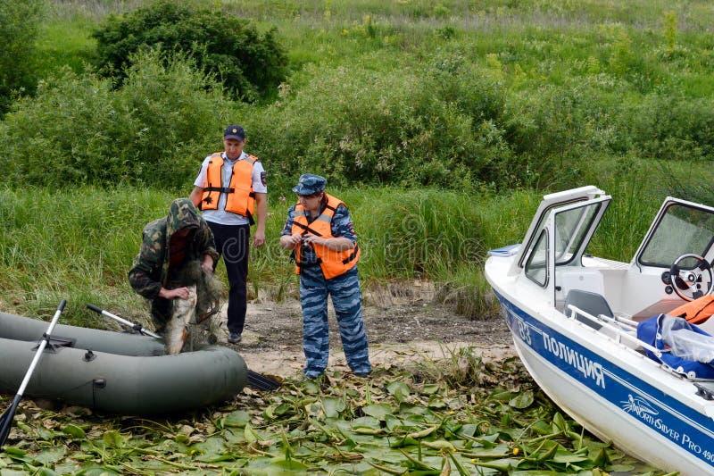 Polizeibeamten stellen ein Protokoll für den Mann für das Pochieren auf dem Oka-Fluss auf stockbild