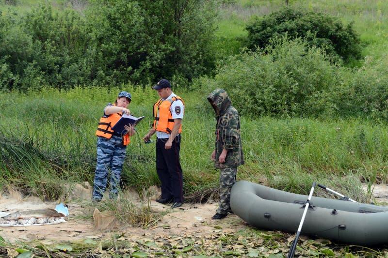 Polizeibeamten stellen ein Protokoll für den Mann für das Pochieren auf dem Oka-Fluss auf lizenzfreies stockfoto