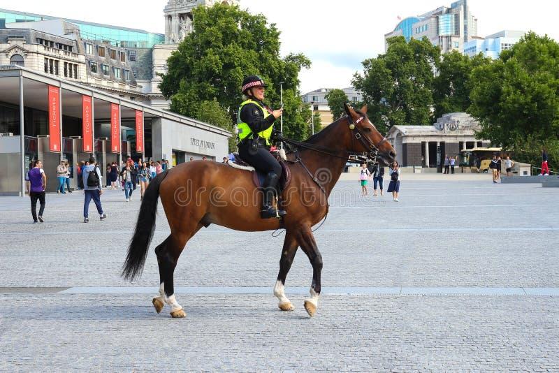 Polizeibeamtin führt an Verkehr vom Pferderuecken nahe Tower von London Polizei zu Pferd in Großbritannien für die Verhinderung v lizenzfreie stockfotos