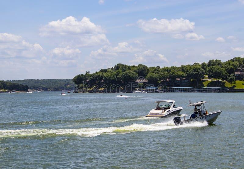 Polizeiboot, das durch das Wasser mit Häusern und Bootsdocks auf dem Ufer und andere Boote und PWCs weit heraus auf den See - G R stockfoto