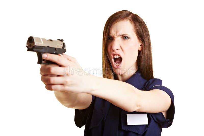 Polizeifrauenzündung ihre Waffe stockfoto