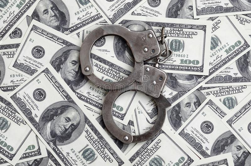 Polizeihandschellenlüge auf vielen Dollarscheinen Das Konzept des illegalen Besitzes des Geldes, illegale Geschäfte mit US-Dollar stockfotos