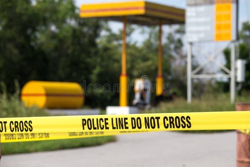 Polizeilinie tun kein Kreuz mit Tankstellehintergrund in Verbrechen sce stockfoto