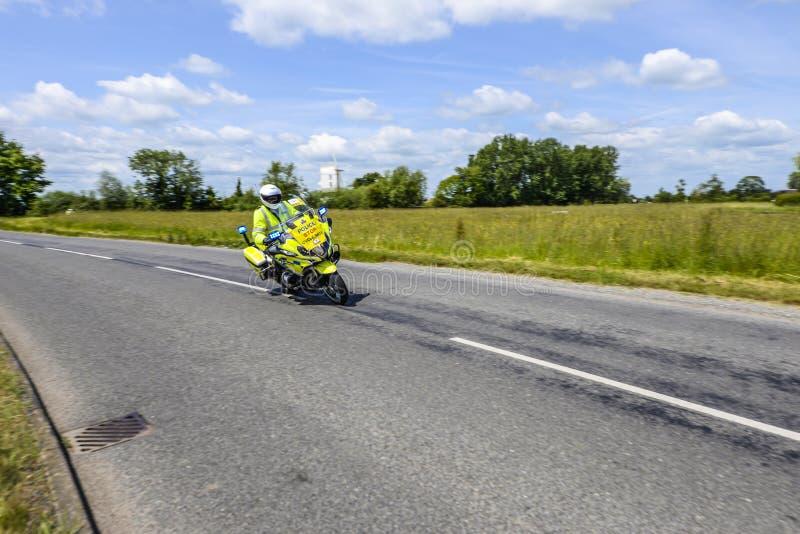 Polizeimotorrad-Eskorte auf dem Motorrad-Reiten mit Geschwindigkeit durch britische Landschaft lizenzfreie stockfotografie