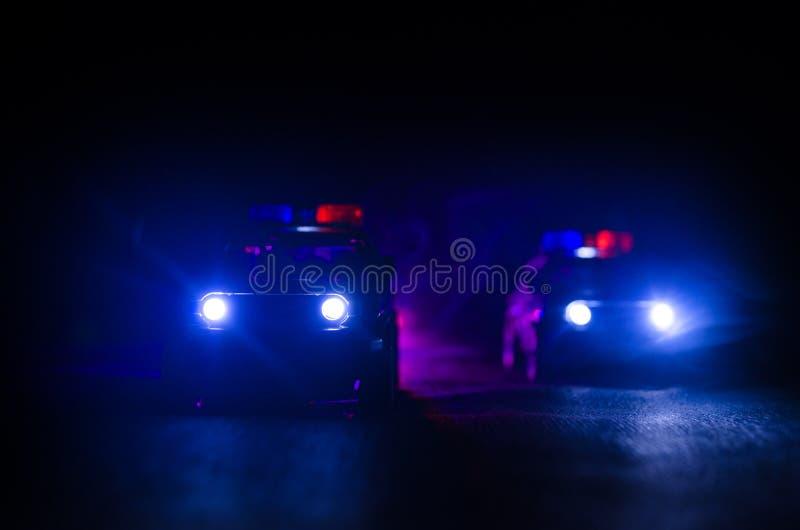 Polizeiwagen, der ein Auto nachts mit Nebelhintergrund jagt Polizeiwagen mit 911 Notfallschutzen, der zur Szene des Verbrechens b stockbilder