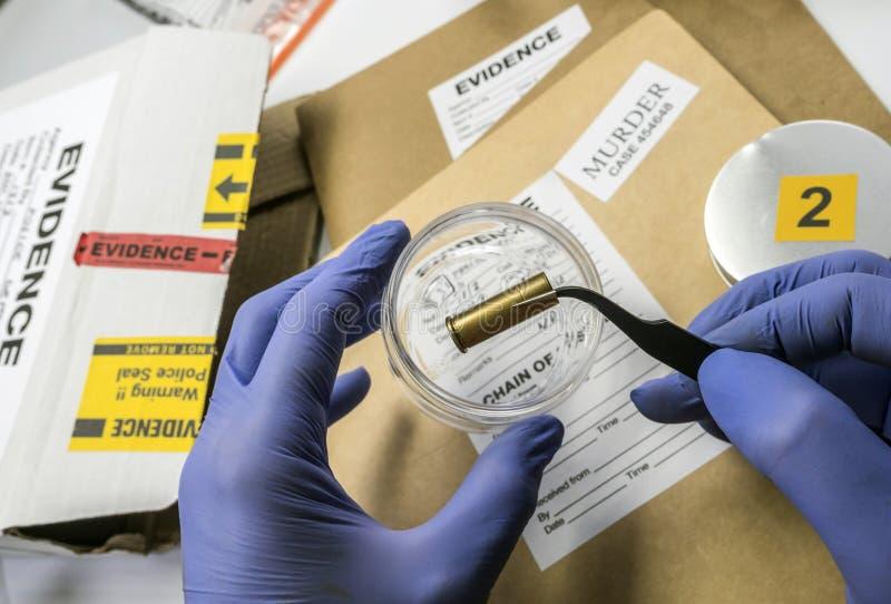 Polizia scientifica che esamina un cappuccio della pallottola in laboratorio balistico fotografia stock