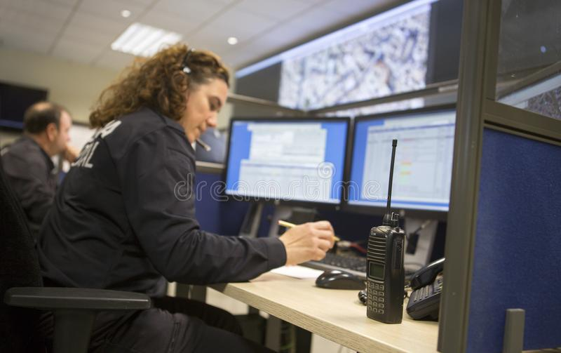 Poliziotta al centro di controllo di sorveglianza immagine stock