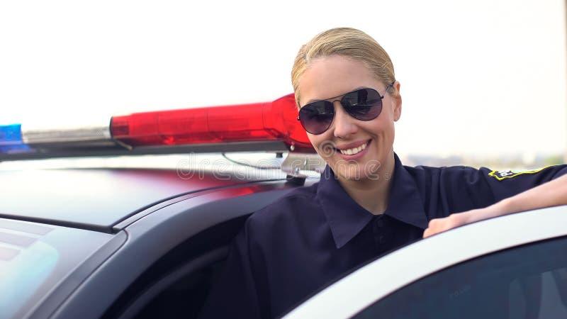 Poliziotta in occhiali da sole che sorride, esaminando macchina fotografica, stante vicino alla pattuglia della polizia fotografia stock libera da diritti