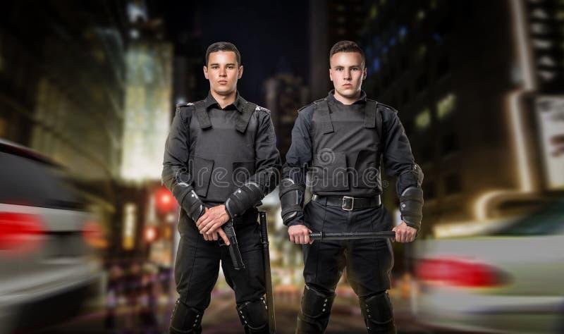 Poliziotti con la pistola e un bastone in guardia di legge fotografia stock