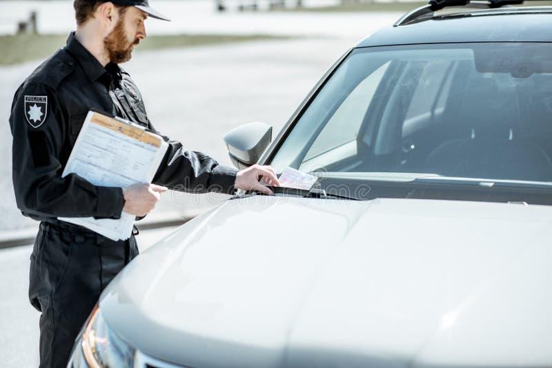 Poliziotto che mette benissimo sull'automobile fotografia stock libera da diritti