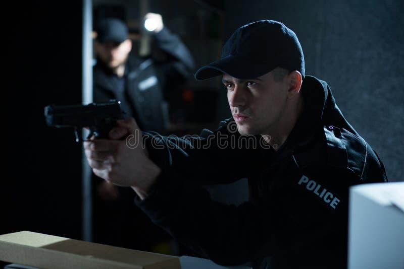 Polizist, der Gewehr während der Aktion zielt stockfotos