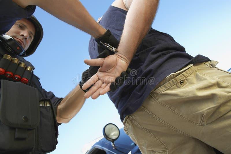 Polizist, der Verbrecher gegen Himmel festnimmt lizenzfreies stockfoto