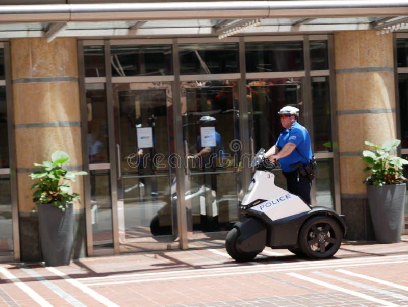 Polizist patrouillieren die Straßen auf elektrischem Roller lizenzfreie stockbilder