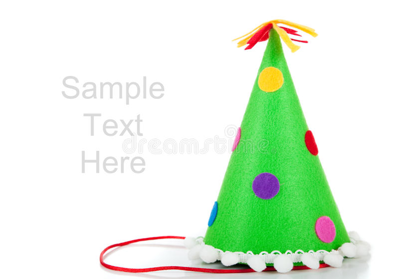 Polka-dot birthday hat onwhite with copy space. Green polka-dotted birthday hat on white with copy space royalty free stock image