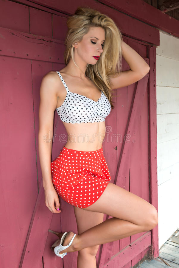 Polka dots. Beautiful tall nude blonde in red and white polka dots royalty free stock photography