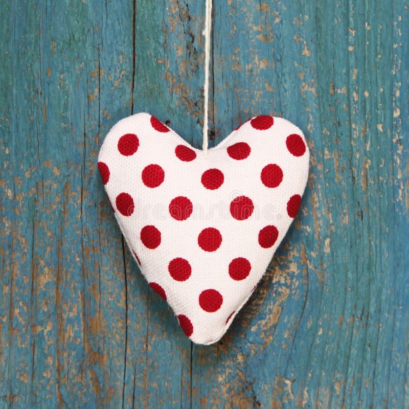 Polka gestippeld hart op turkooise houten oppervlakte in de stijl van het land. stock afbeelding