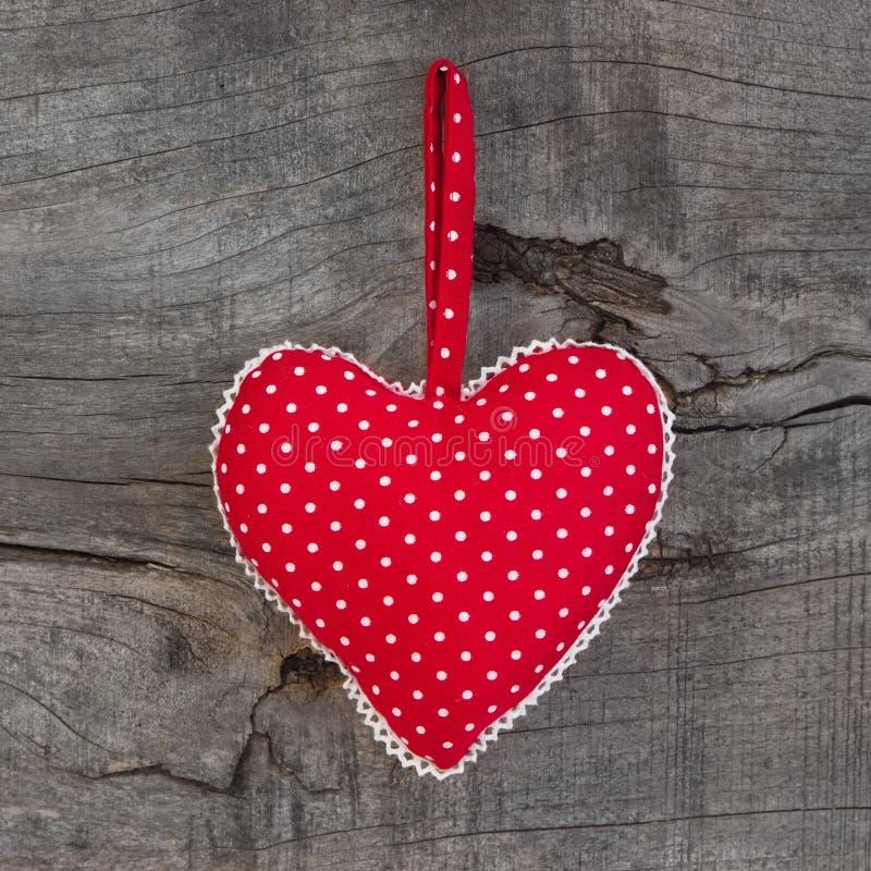Polka het gestippelde hartvorm hangen op een houten achtergrond voor Dal royalty-vrije stock foto's