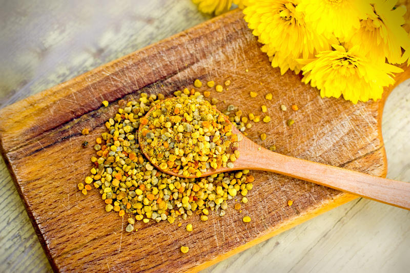 Pollen granules in wooden spoon royalty free stock photos