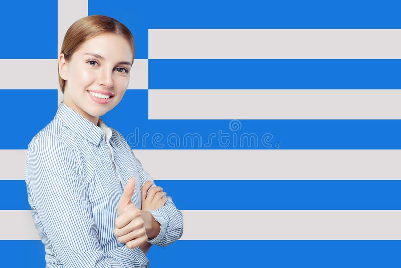 Pollice allegro di rappresentazione della giovane donna su con la bandiera della Grecia immagine stock libera da diritti