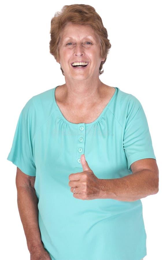 Pollice felice sorridente della donna anziana maggiore matura in su immagini stock