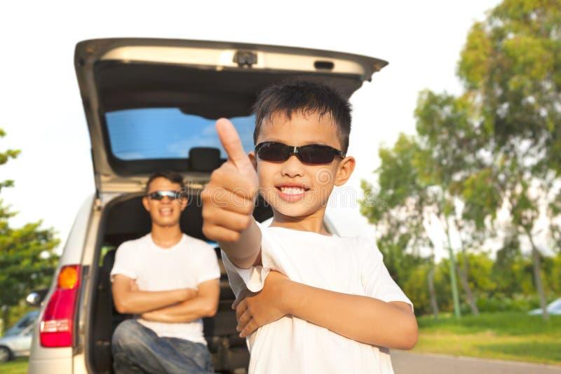 Pollice fresco del ragazzo alto e padre attraverso le armi con l'automobile fotografia stock
