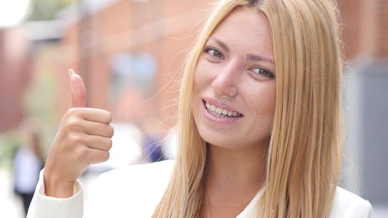 Pollice su dalla ragazza sorridente, ritratto all'aperto fotografia stock