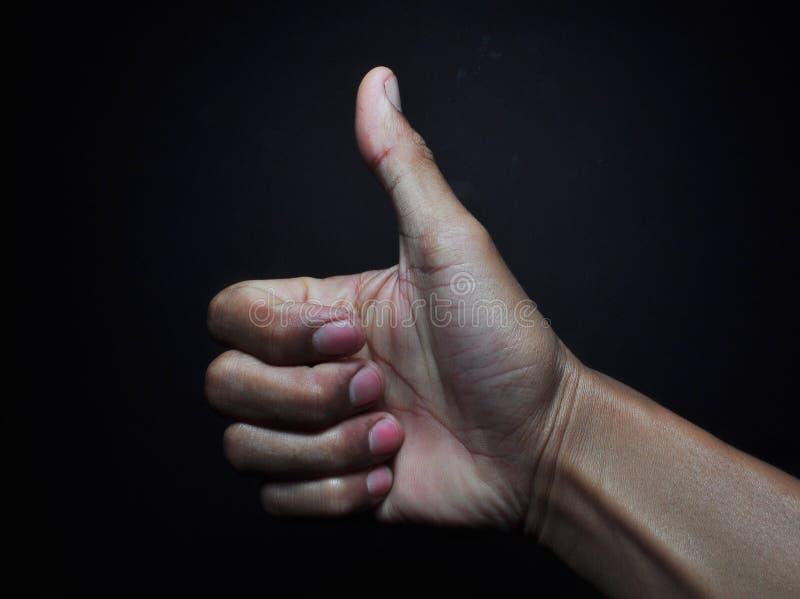 Pollice sul gesto di mano isolato su fondo nero immagini stock