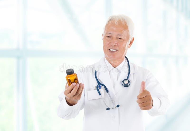 Pollice sulle pillole asiatiche della bottiglia della tenuta di medico fotografie stock