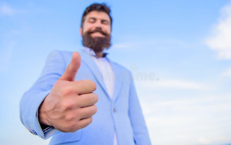 Pollici barbuti allegri di manifestazione dell'uomo d'affari dell'uomo sul fondo del cielo Pollici di manifestazione dei pantalon fotografia stock