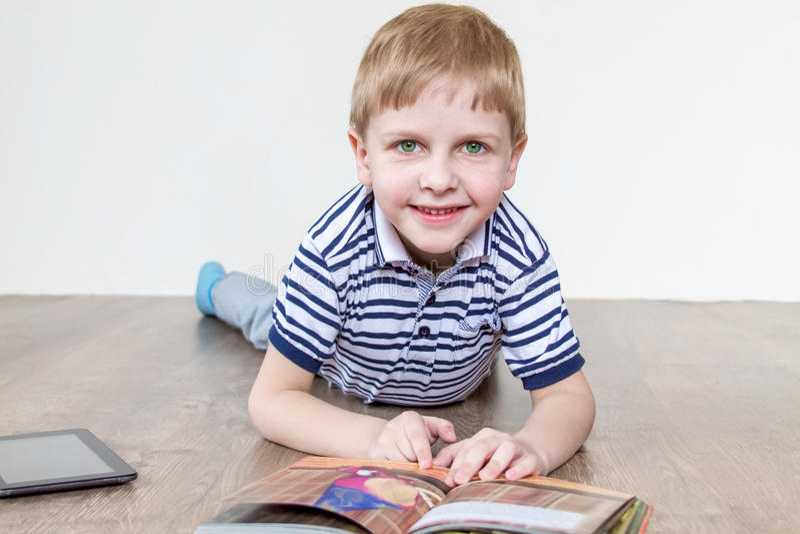 Pollici del ragazzo attraverso il libro fotografia stock