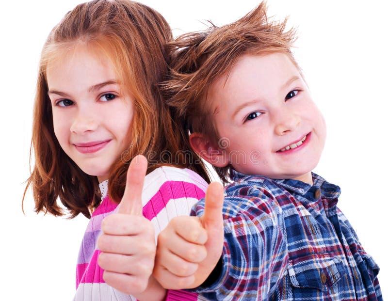 Pollici felici della ragazza e del ragazzo in su fotografia stock libera da diritti