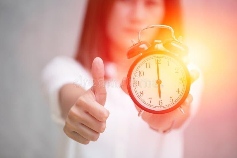 Pollici su con un orologio per buon tempo immagini stock libere da diritti
