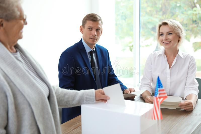 Polling station workers near ballot box. At table indoors stock image