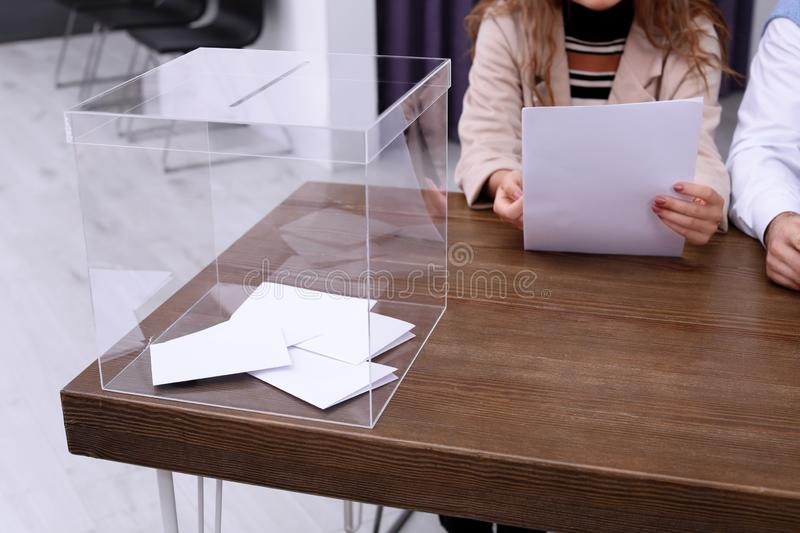 Polling station workers at table. With ballot box royalty free stock photography