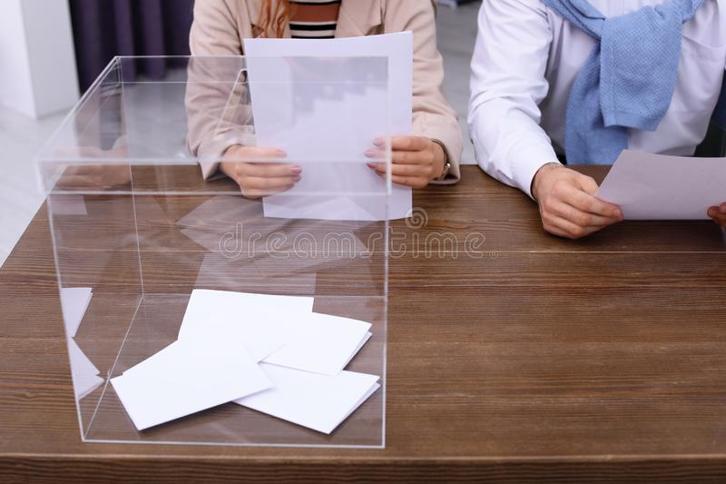 Polling station workers at table. With ballot box royalty free stock image