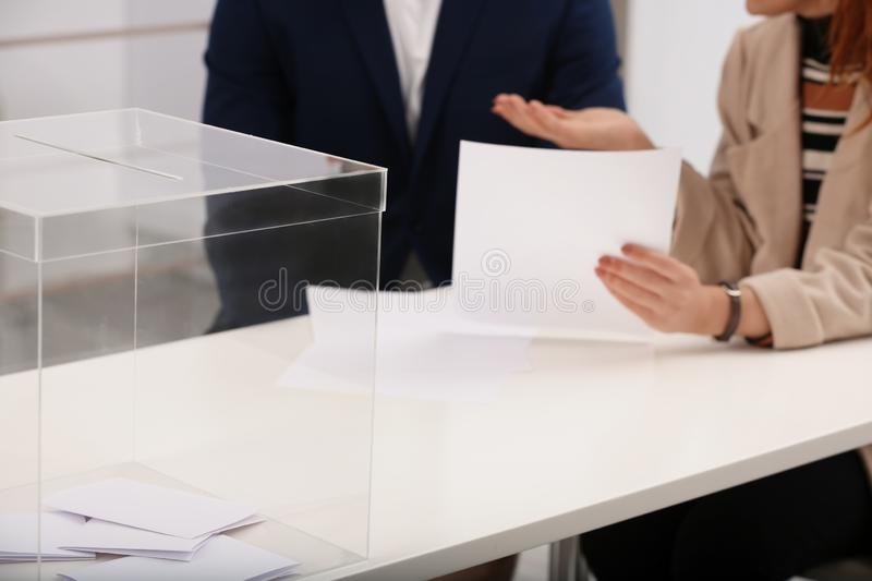 Polling station workers at table. With ballot box stock images