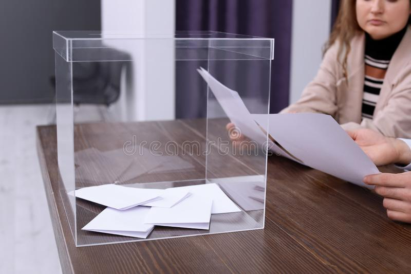 Polling station workers at table. With ballot box royalty free stock photos