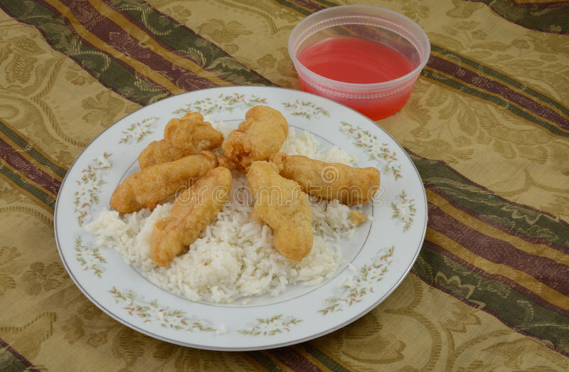 Pollo agridulce con el arroz blanco y la salsa en la placa foto de archivo