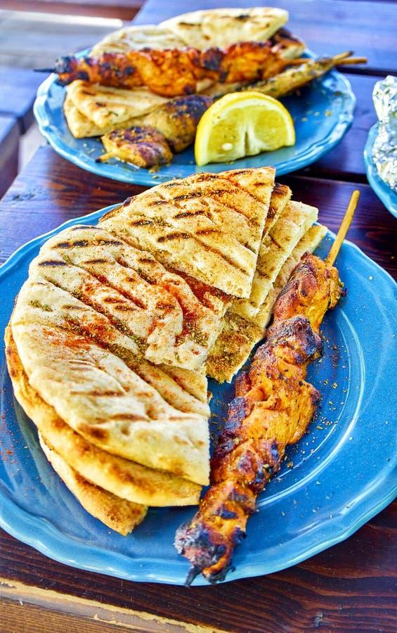 Pollo aromatizzato Souvlakis con l'esperto pane della pita Greco tipico immagine stock