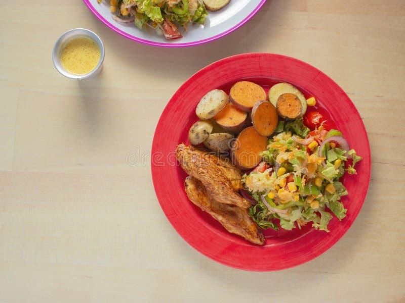 Pollo arrostito affumicato con la salsa del BBQ e una miscela delle patate e patate dolci ed insalata verde con cereale giallo immagine stock